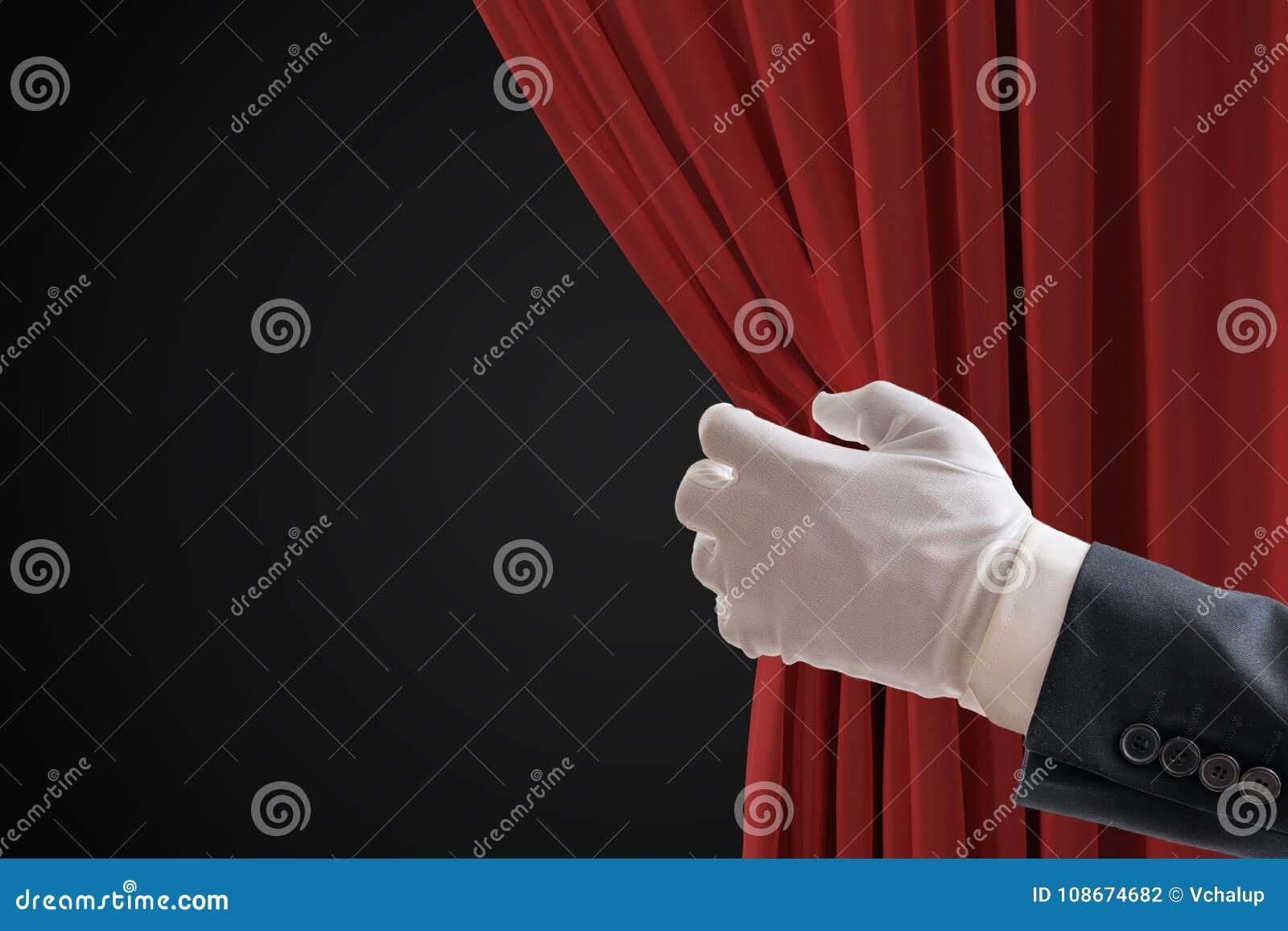 De acteur trekt rode gordijnen in theater met hand