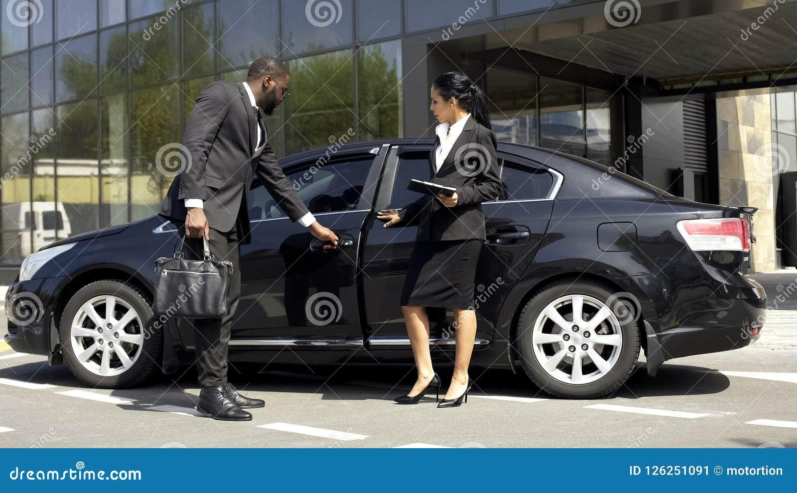 De adviseur die van de autotoonzaal luxeauto tonen aan koper, voertuig die zaken huren