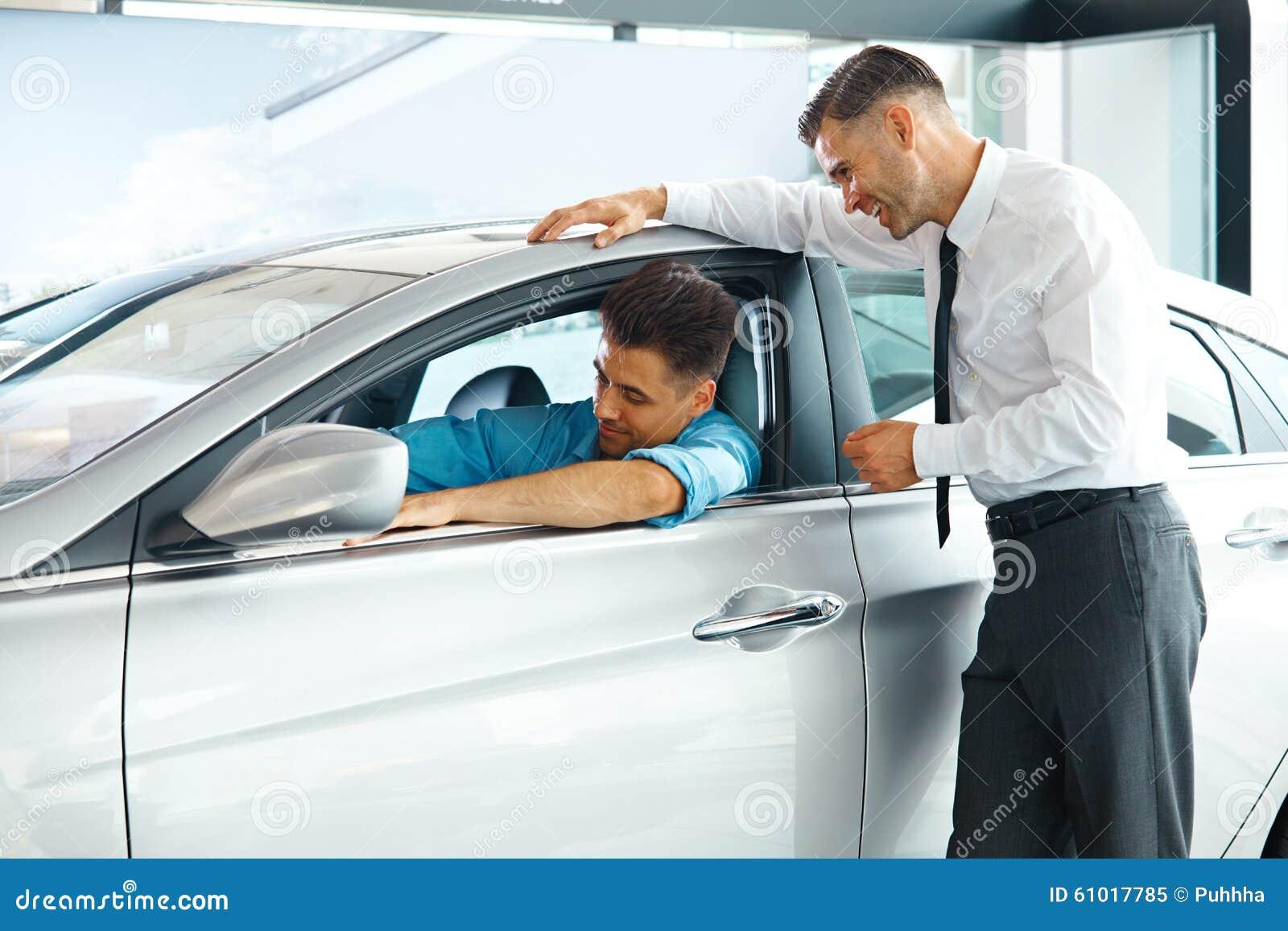 De Adviseur Showing van de autoverkoop een Nieuwe Auto aan een Potentiële Koper in S