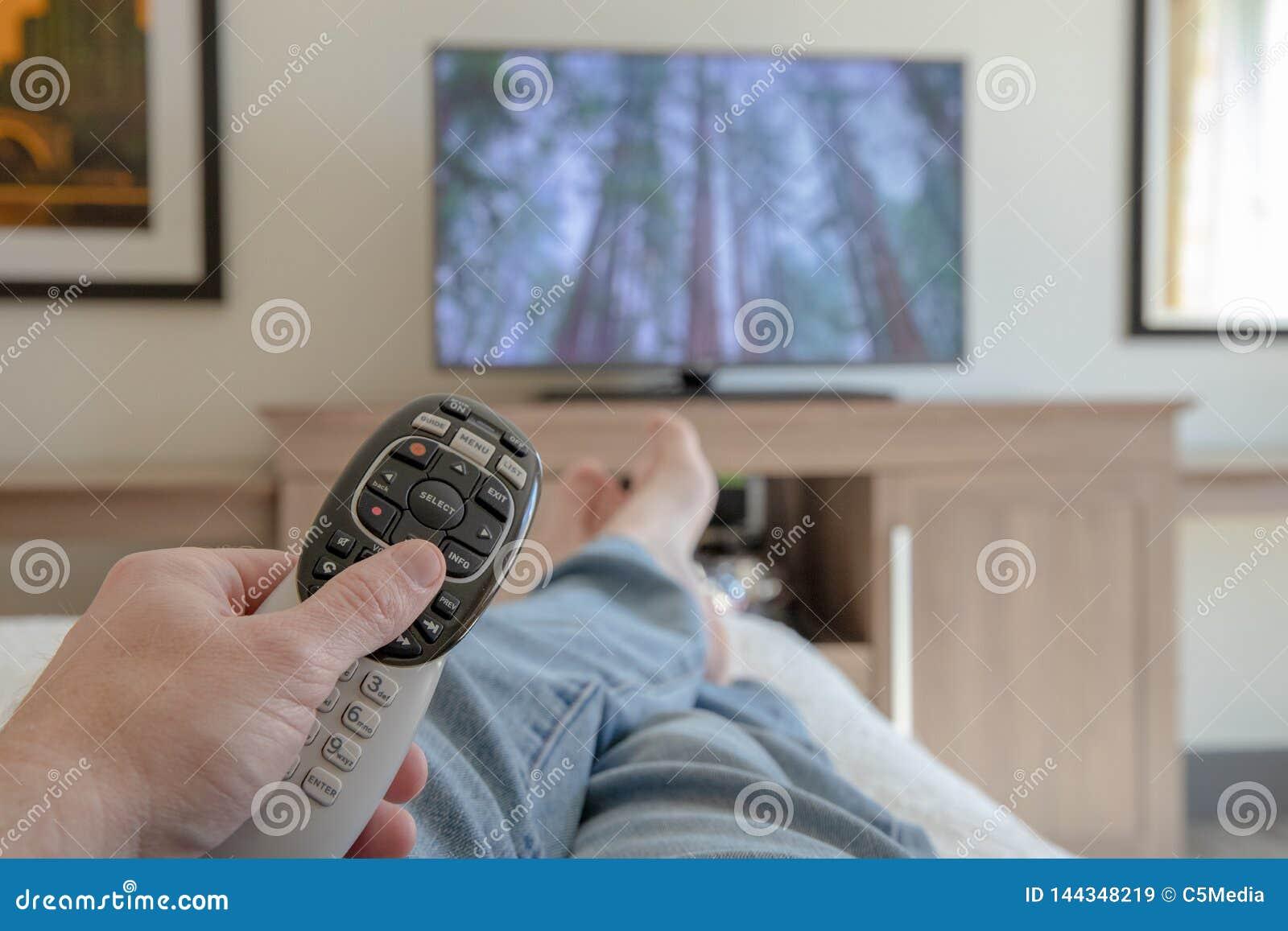De afstandsbediening van de handholding voor TV terwijl het ontspannen met voeten propped omhoog - Ondiepe velddiepte