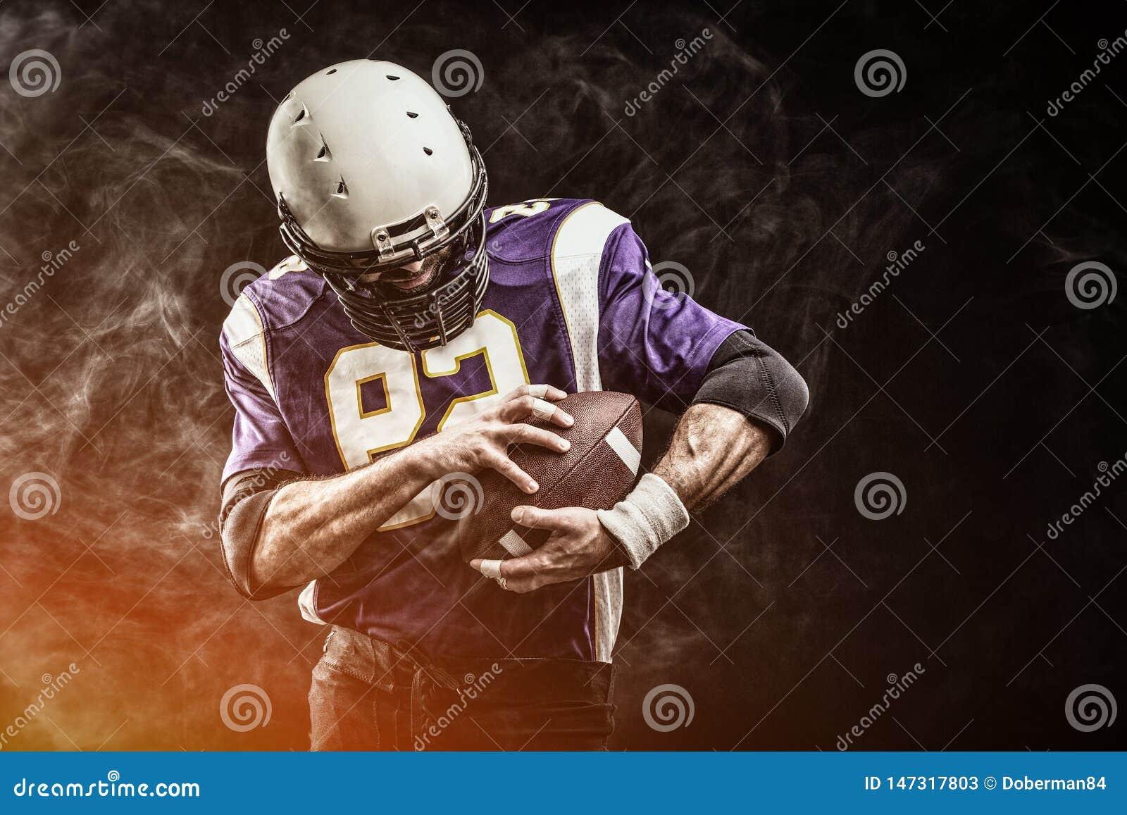 De Amerikaanse bal van de voetbalsterholding in van hem dient rook in zwarte achtergrond, exemplaarruimte Het concept Amerikaan