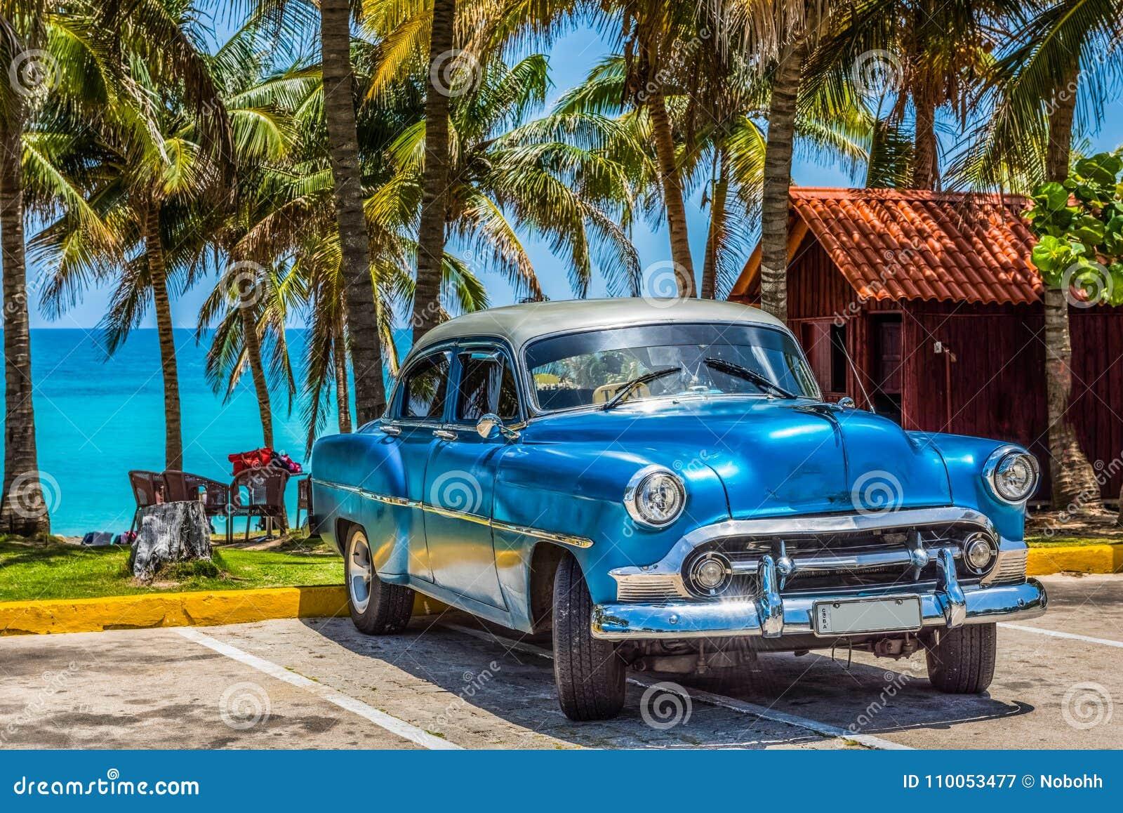 De Amerikaanse blauwe klassieke auto van Chevrolet met zilveren die dak op het strand in Varadero Cuba - de Rapportage van Serie