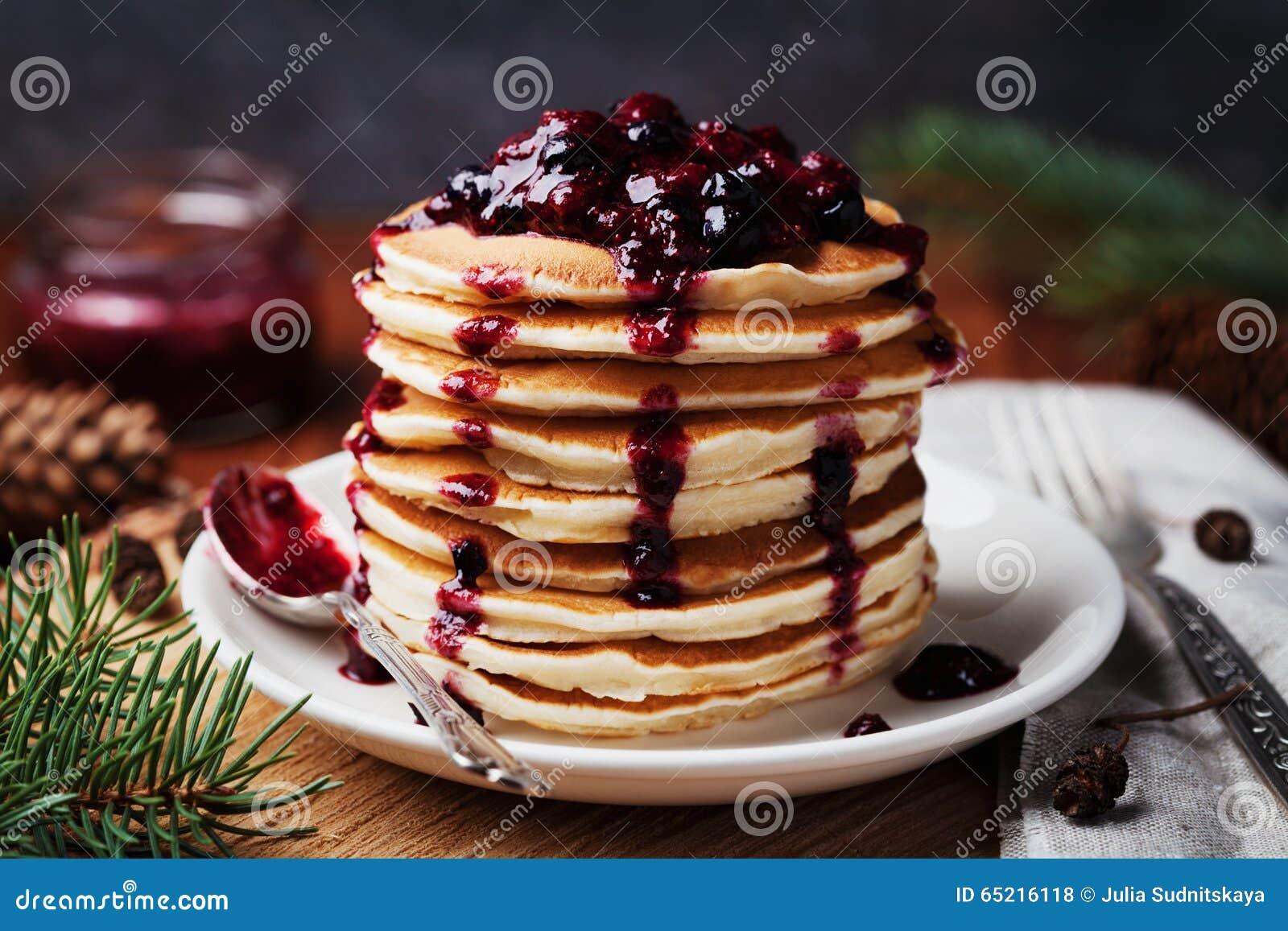De Amerikaanse pannekoeken of fritters dienden met aardbei en bosbessenjam, heerlijk dessert voor ontbijt in de winter