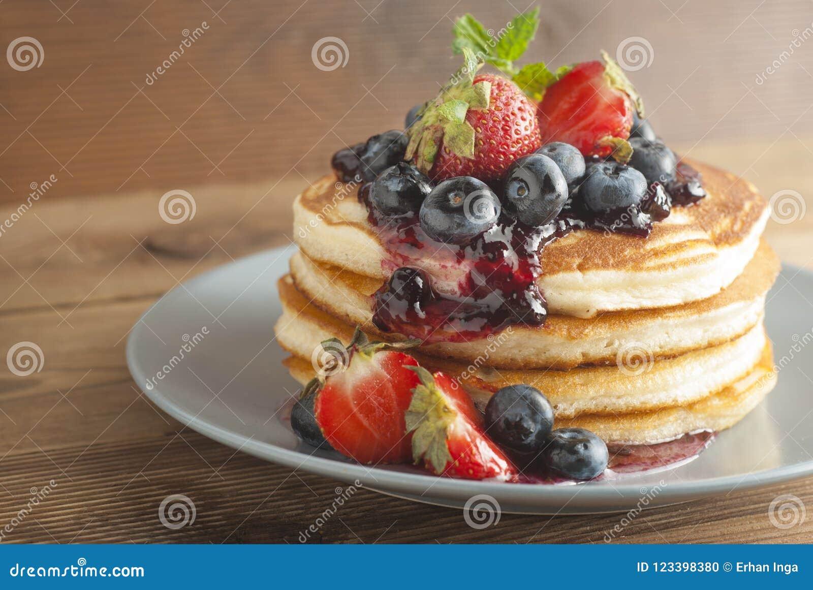 De Amerikaanse pannekoeken of fritters dienden met aardbei en bosbessenjam, heerlijk dessert voor ontbijt, rustieke stijl, houten