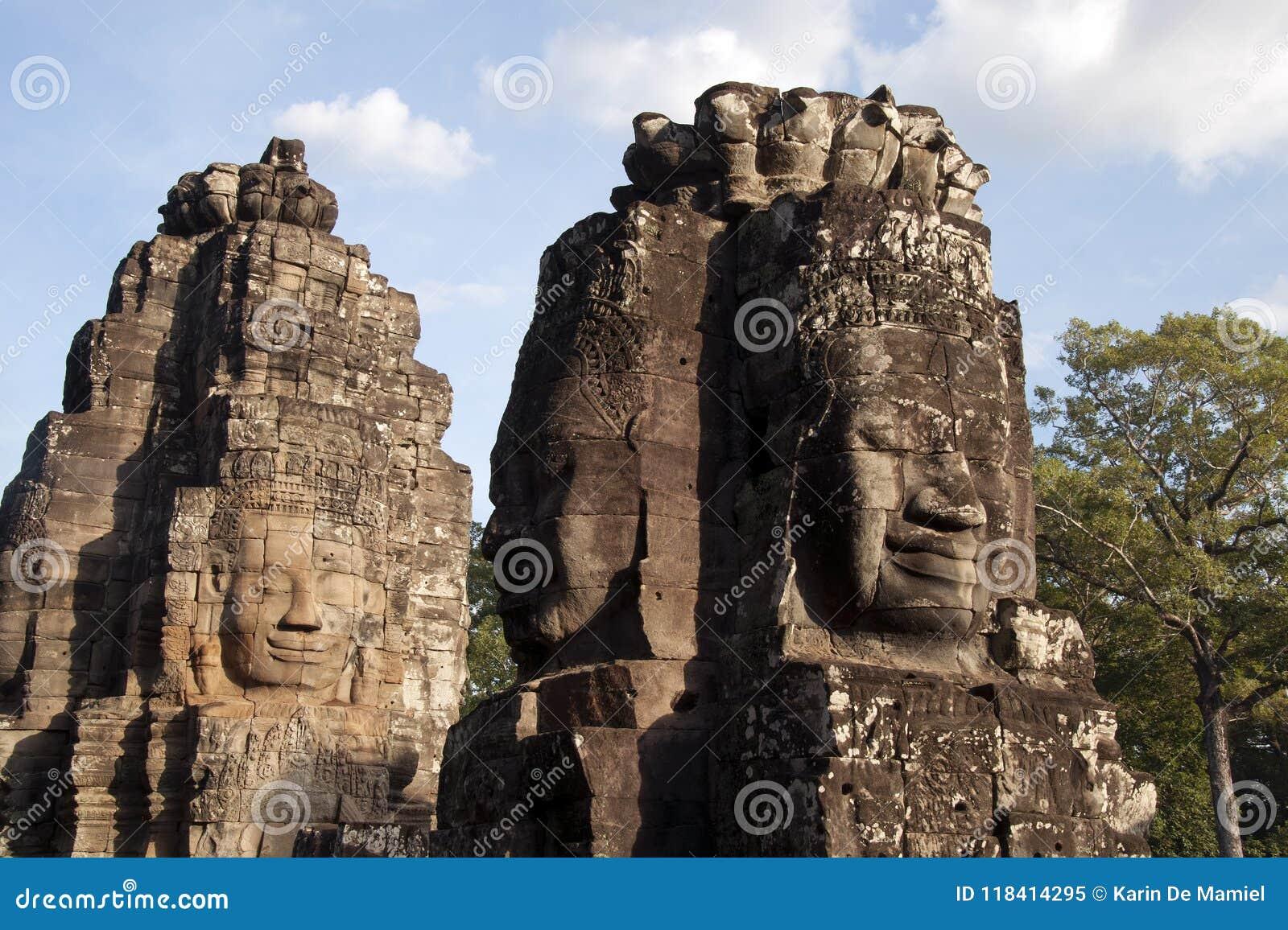 De antropomorfe gezichten sneden in steen in Bayon Wat in recente middaglicht, een de 12de eeuwtempel binnen Com van Angkor Thom