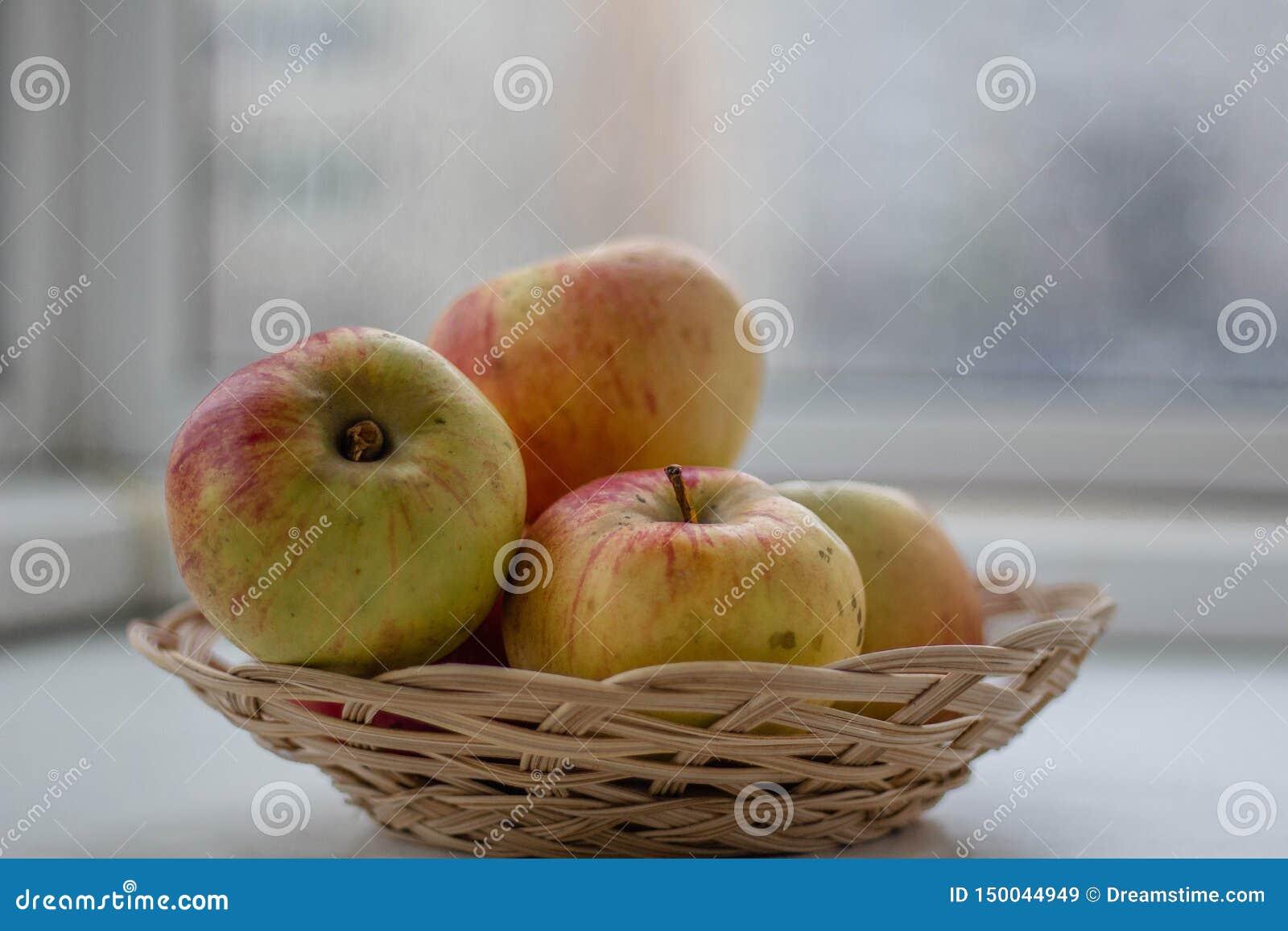 De appelen liggen in een rieten mandclose-up