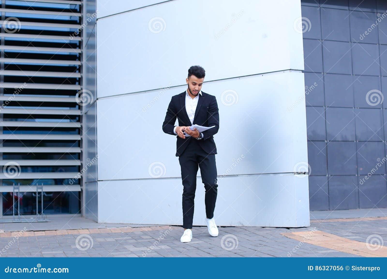 De Arabische mannelijke mensenzakenman verzamelt documenten en documenten dichtbij o