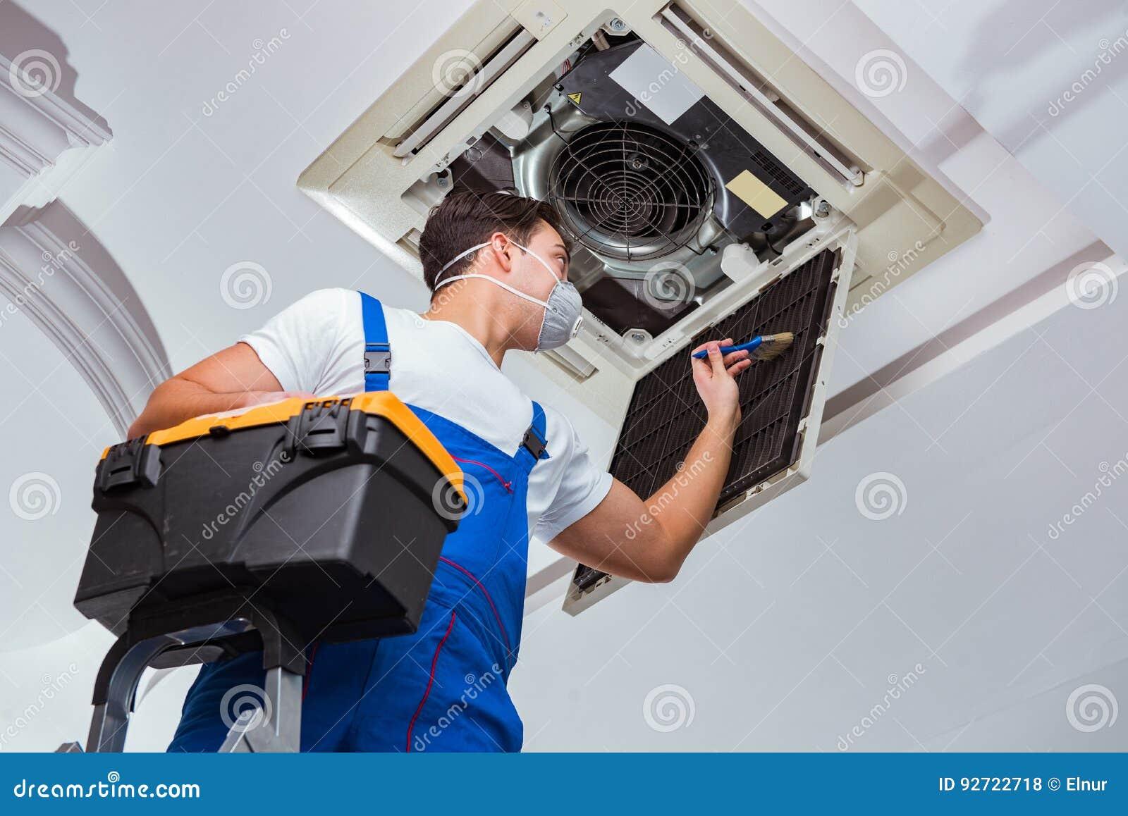 De arbeider die de eenheid van de plafondairconditioning herstellen