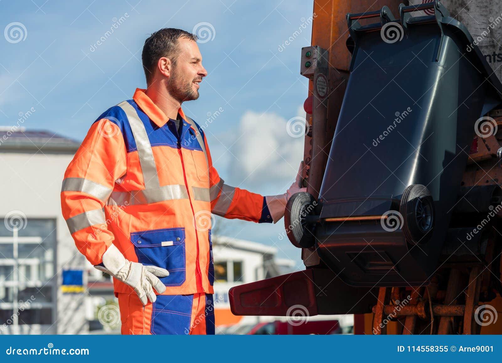 De arbeider die van de huisvuilinzameling bak zetten in afvalvrachtwagen