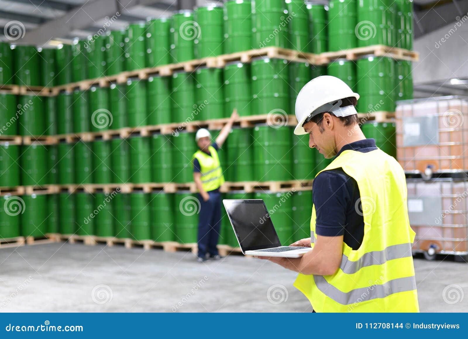 De arbeider in een pakhuis met olievaten controleert de voorraad