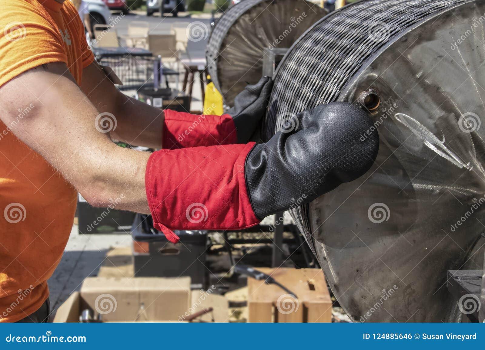 De arbeider houdt voorbereidingen de hete grill van de vatspaanse peper van het draaien tegen en treft om het te openen die op zw