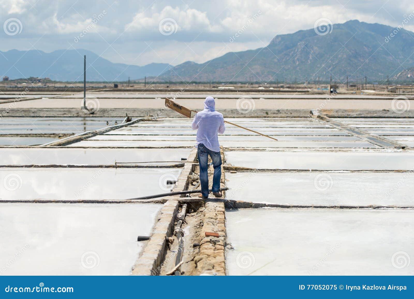 De arbeider met het hulpmiddel gaat voor het zoute gebied werken
