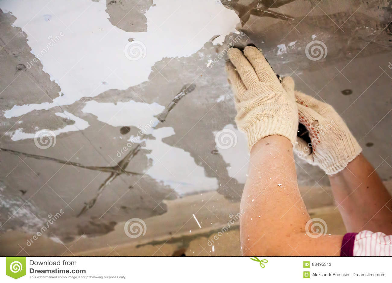 De arbeider schaaft de oude verf