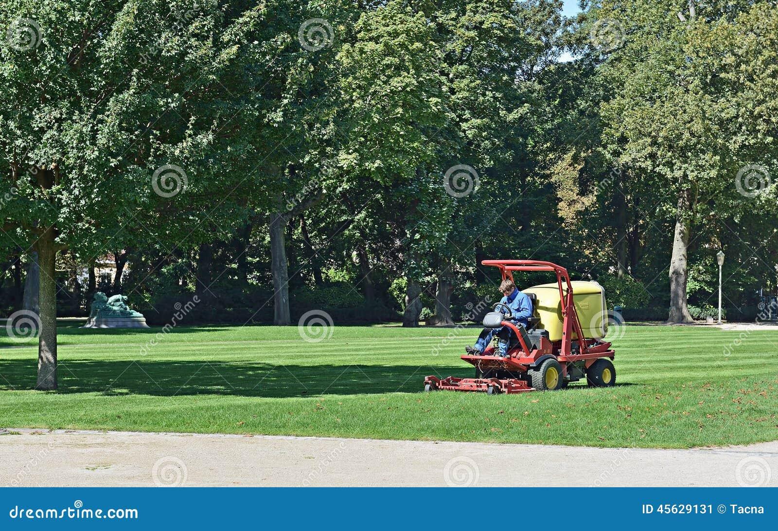 De arbeider snijdt gras in Cinquantenaire Parc in Brussel