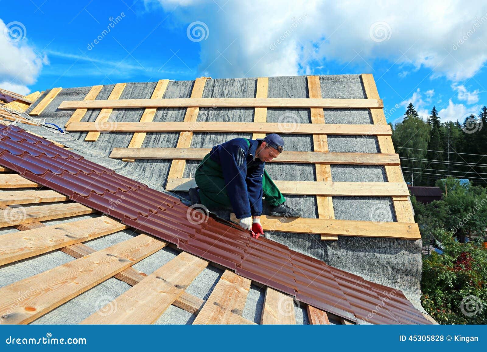 De arbeider zet de metaaltegels op het dak