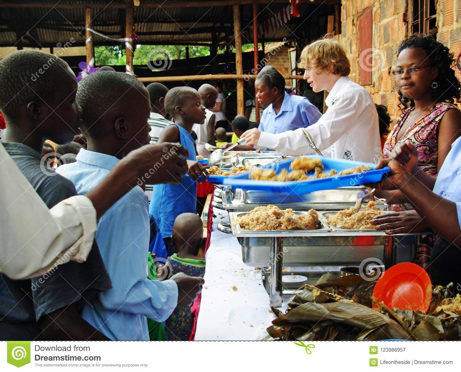 De arbeiders die van de hulpvrijwilligers van de teamhulp hongerige kinderen Afrika voeden