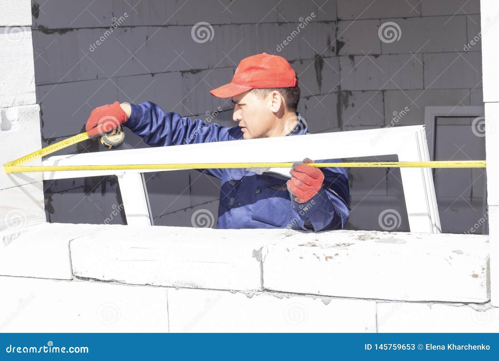 De arbeiders installeren verglazing in aanbouw in een huis