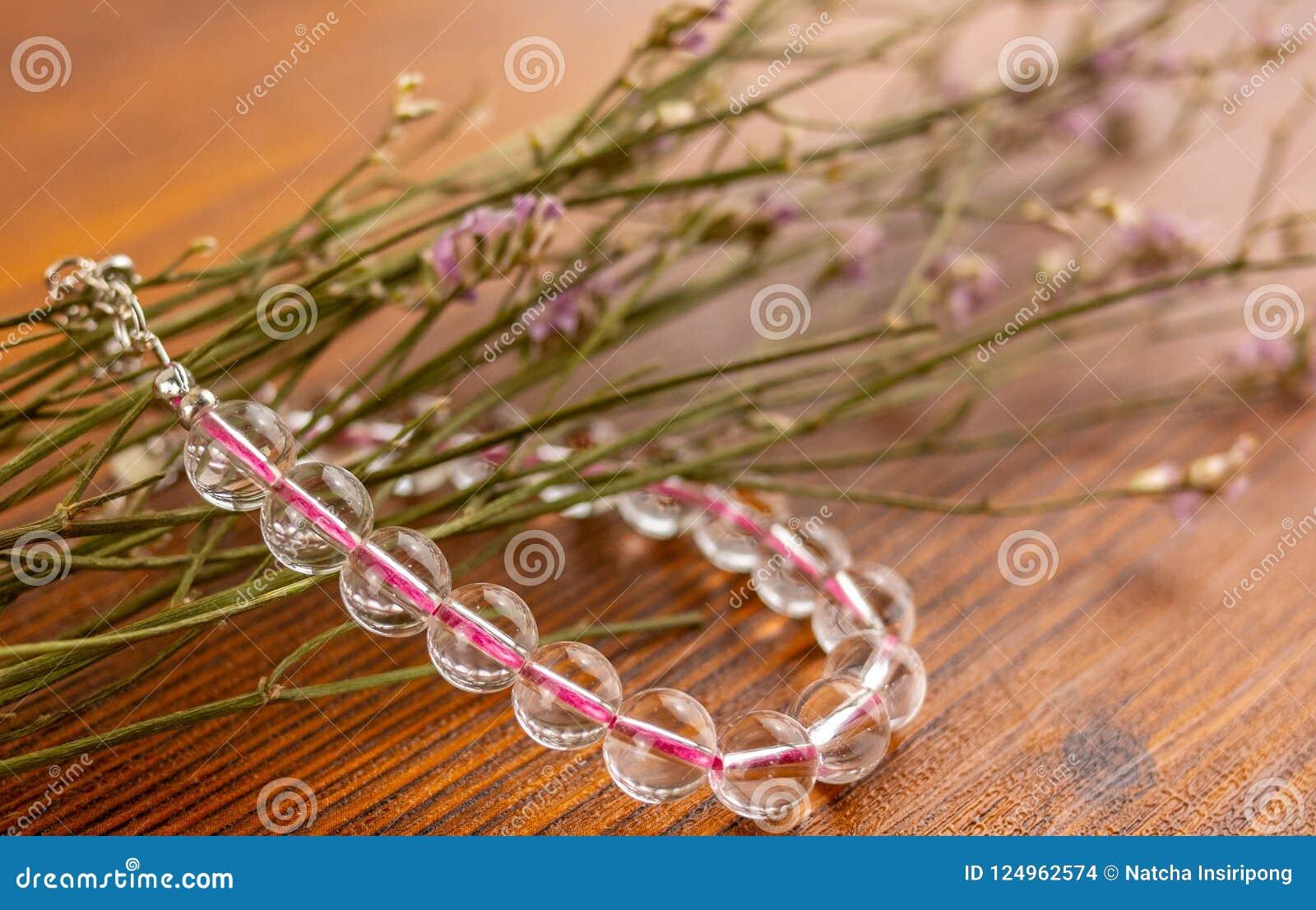 De armband en de bloemen van het kristalkwarts op houten lijst