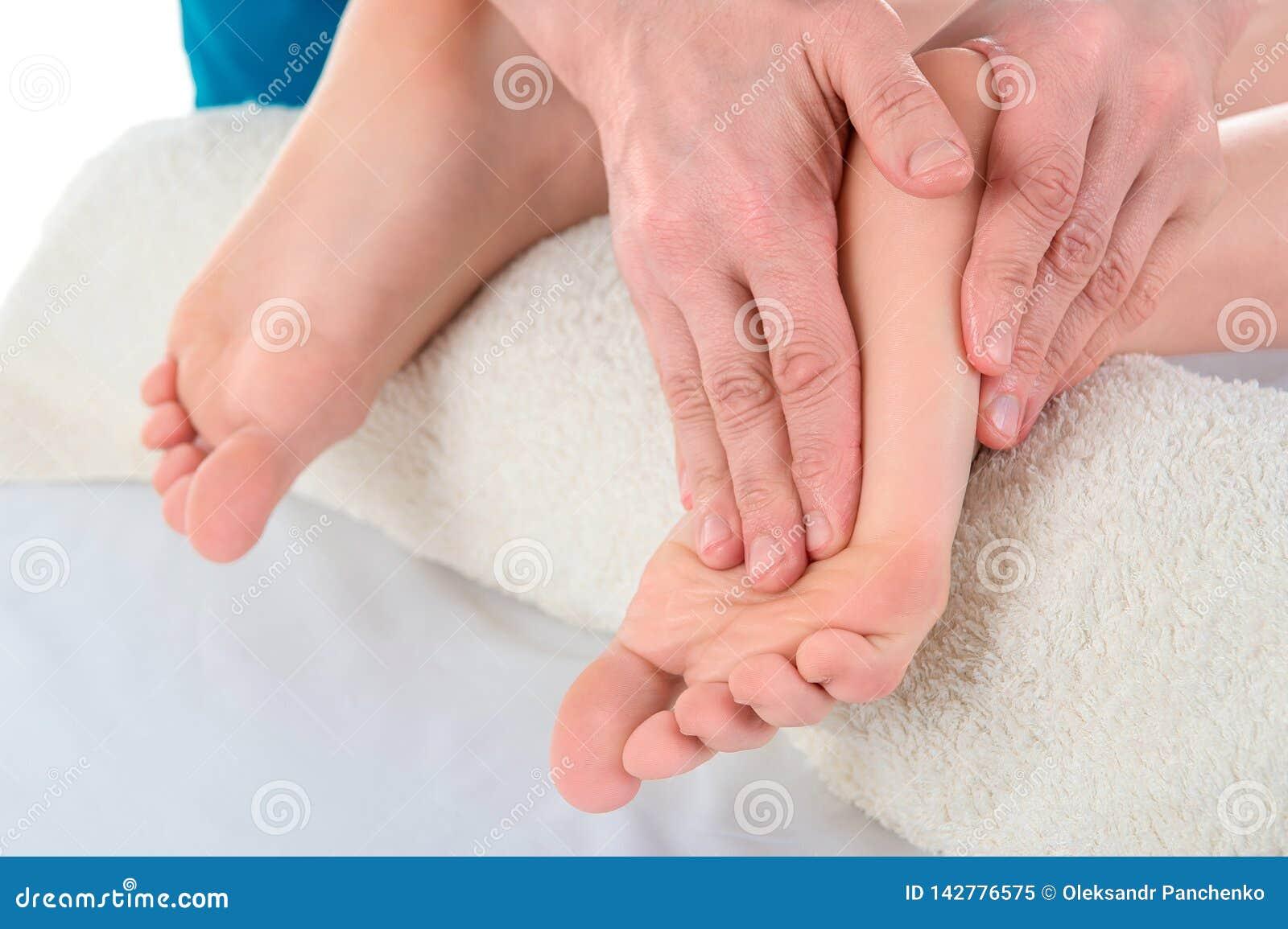 De arts-chiropodist doet een onderzoek en een massage van de geduldige voet van ` s in de kliniek