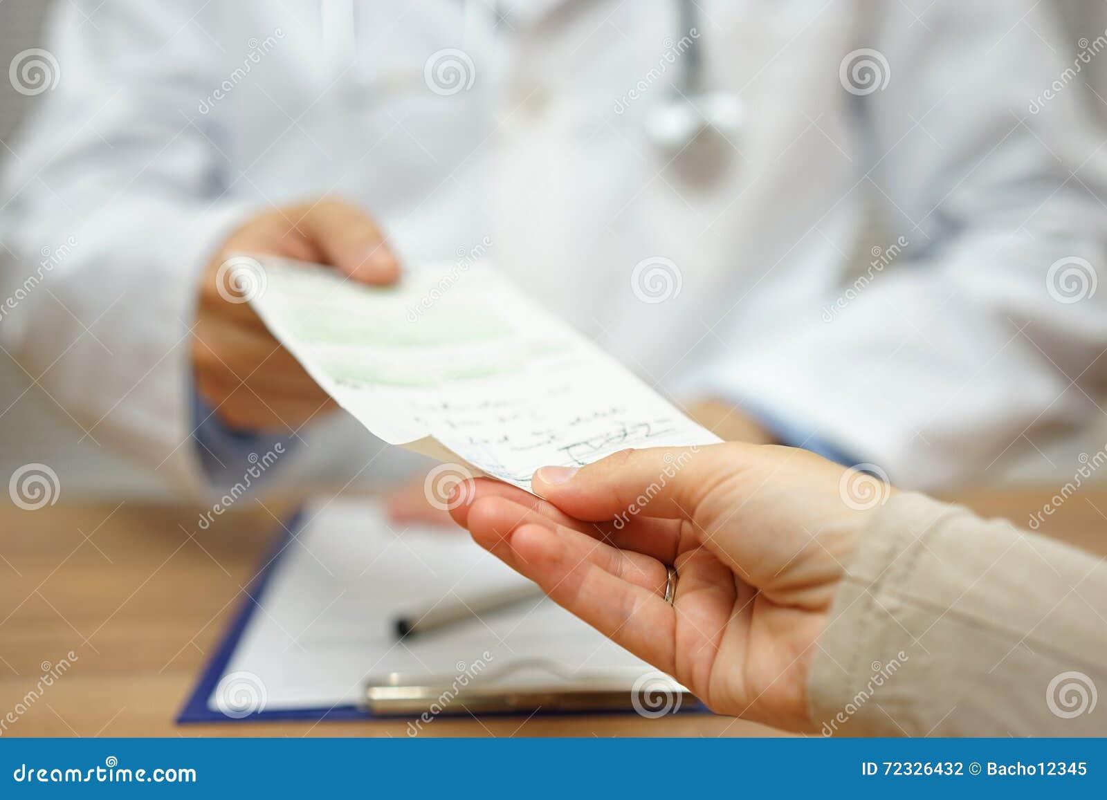 De arts geeft een voorschrift aan een vrouwelijke patiënt
