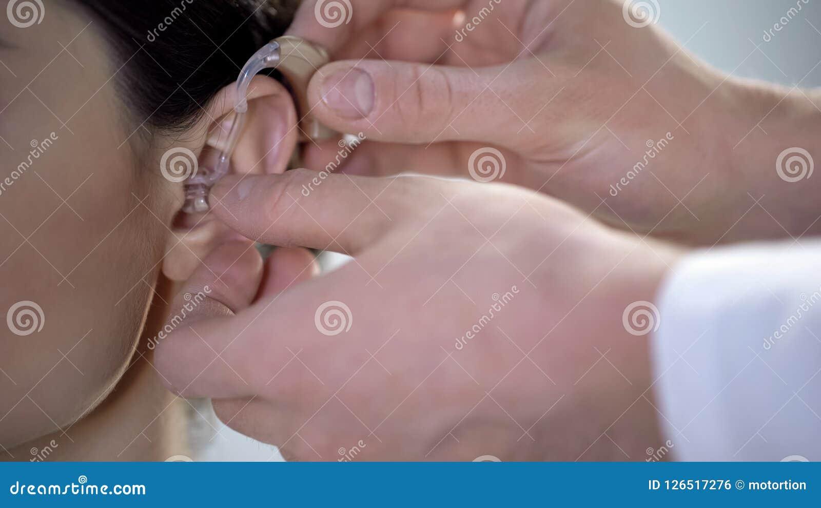 De arts zet dove hulp op jong dameoor, beschadigings van het gehoorbehandeling, hulp