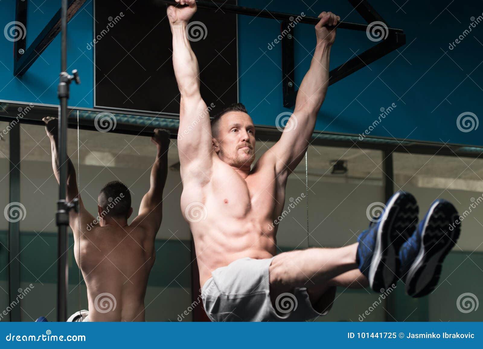 De atleet Performing Hanging Leg heft Oefening op