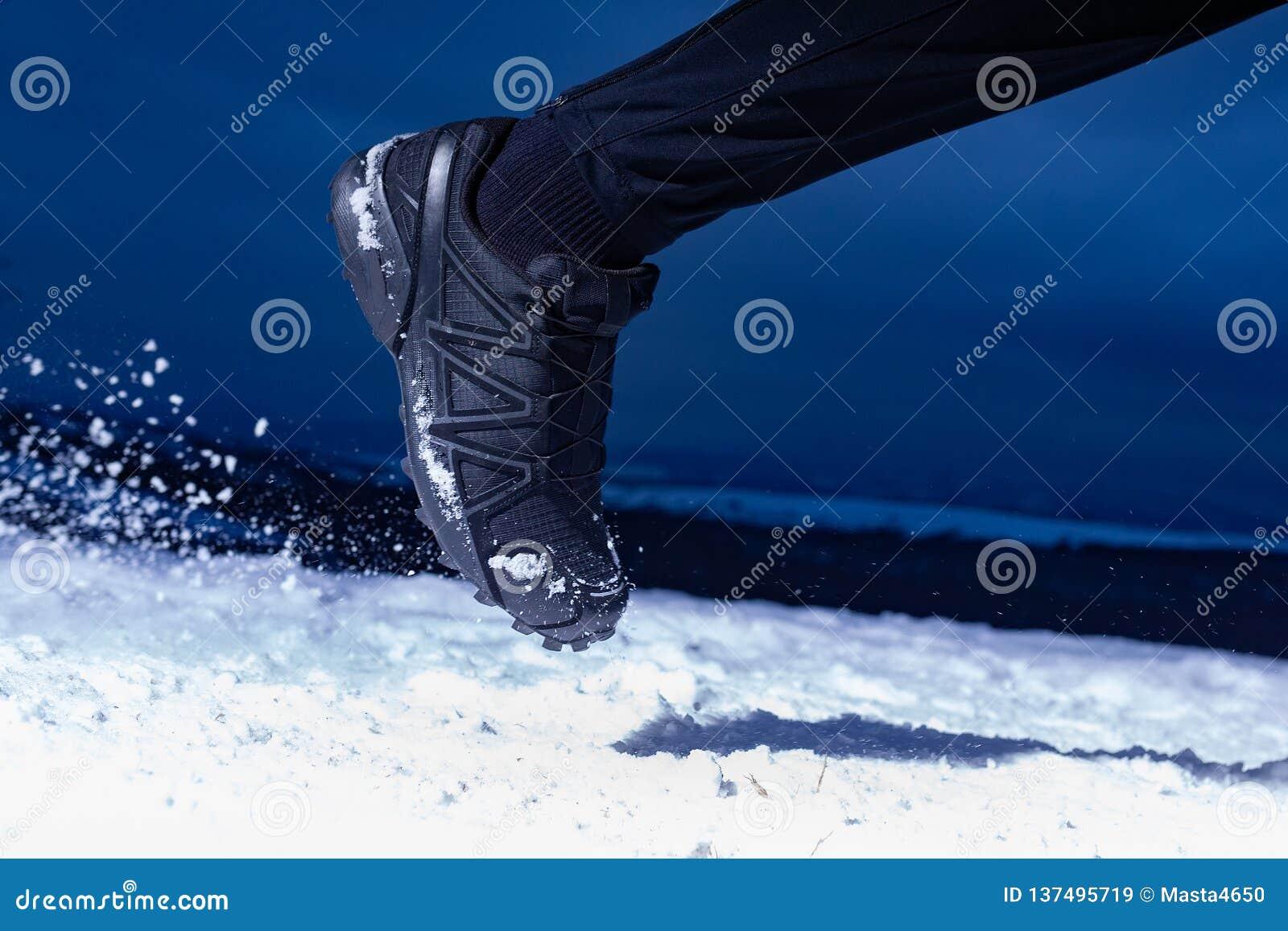 De atletenmens loopt tijdens de winter opleiding buiten in koud sneeuwweer