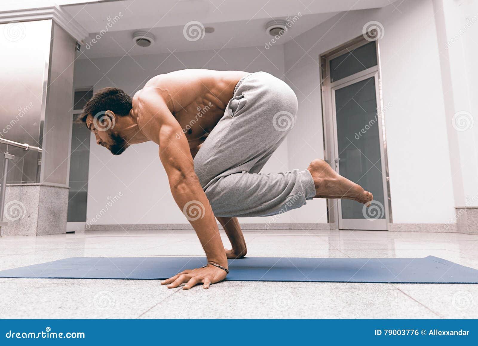 De atletische sterke mens die moeilijke yoga uitoefenen stelt