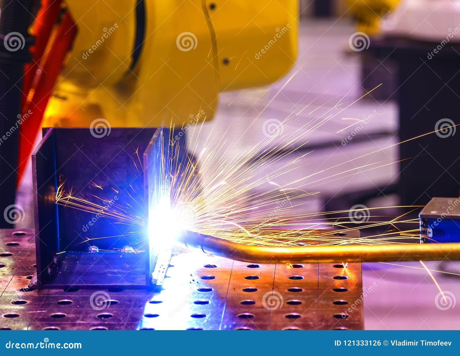 De automatische lassenmachine veroorzaakt lassen van metaaltank close-up van blauwe en gele vlammen met nevel Diepte van gebied o