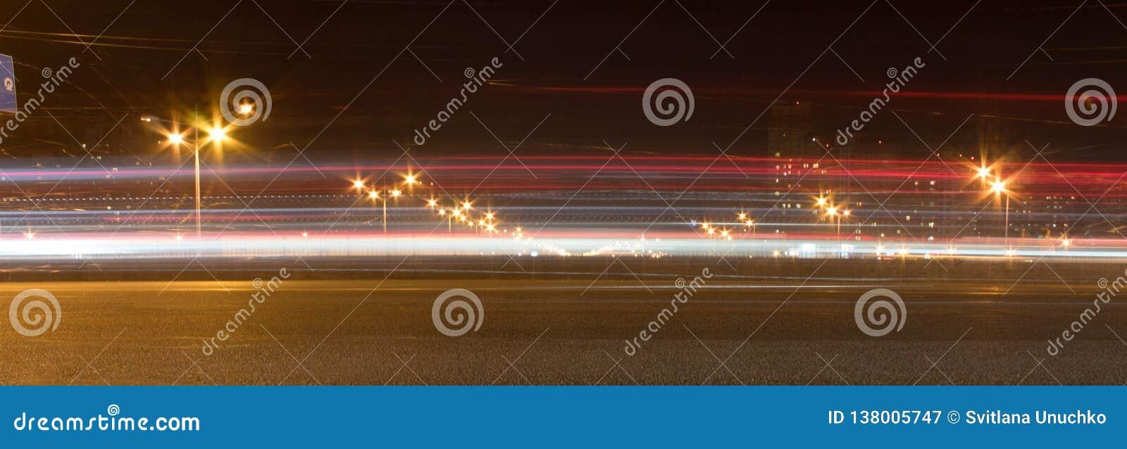 De autosnelweg bij nacht De autobewegingen bij snelle snelheid bij de nacht Bluredweg met lichten met auto op hoge snelheid