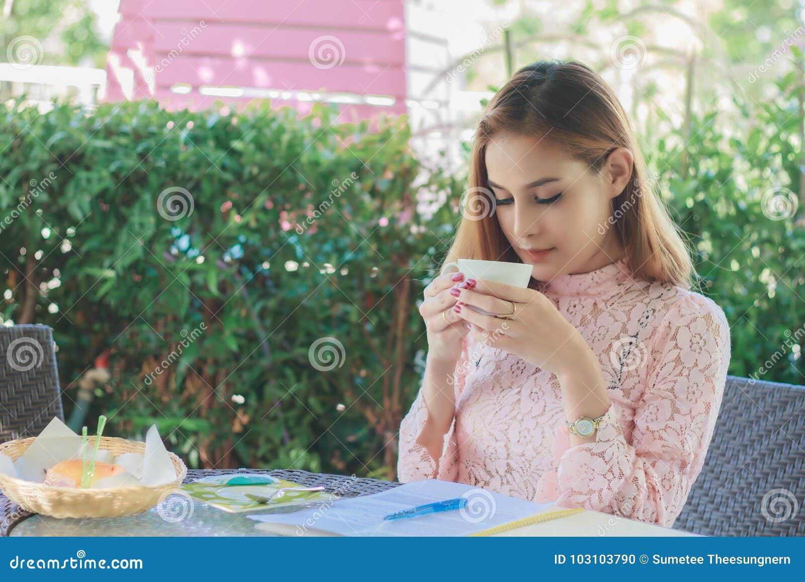 De Aziatische bedrijfsvrouw werkt en drinkt koffie op openlucht