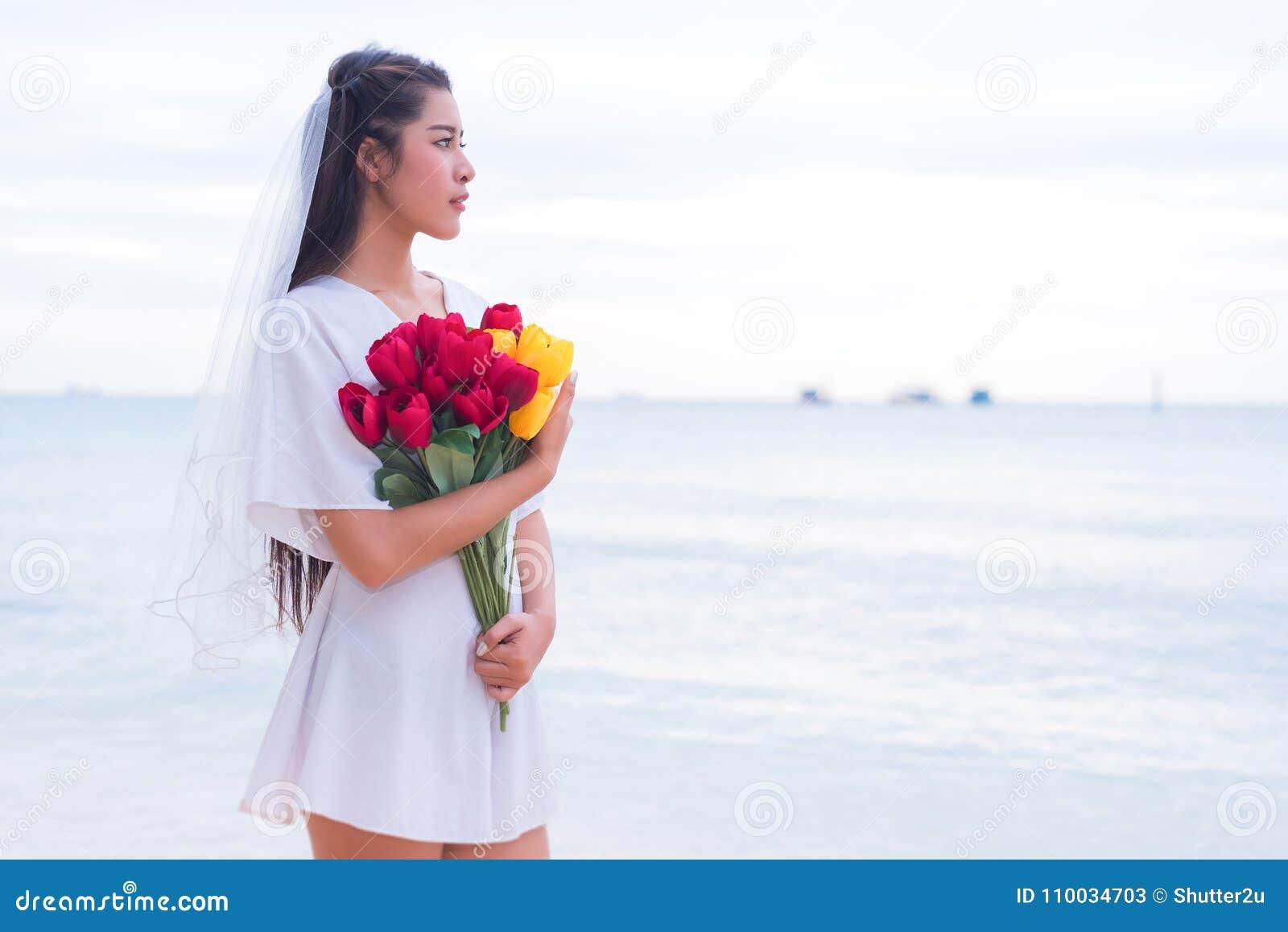 De Aziatische bloemen en het wachten van de vrouwenholding voor iemand maken haar hap