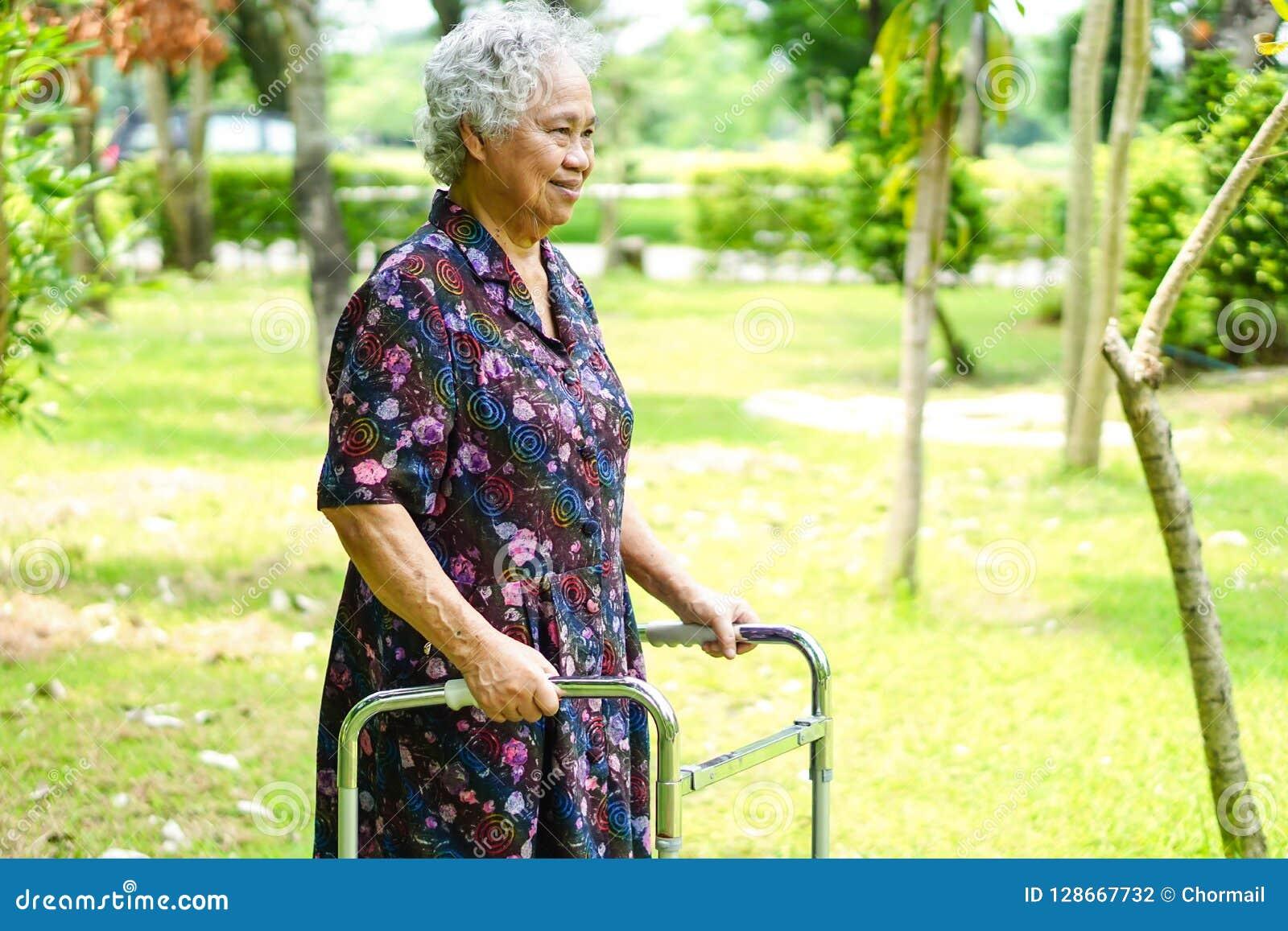 De Aziatische hogere of bejaarde oude geduldige gang van de damevrouw met leurder in park: gezond sterk medisch concept