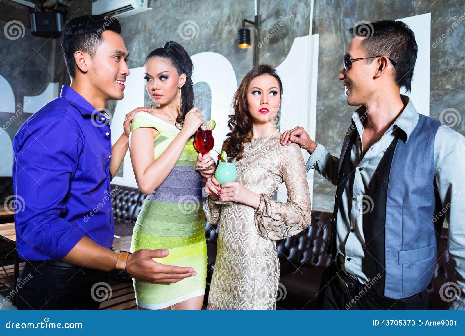 De Aziatische jonge partij koppelt het drinken cocktails in club