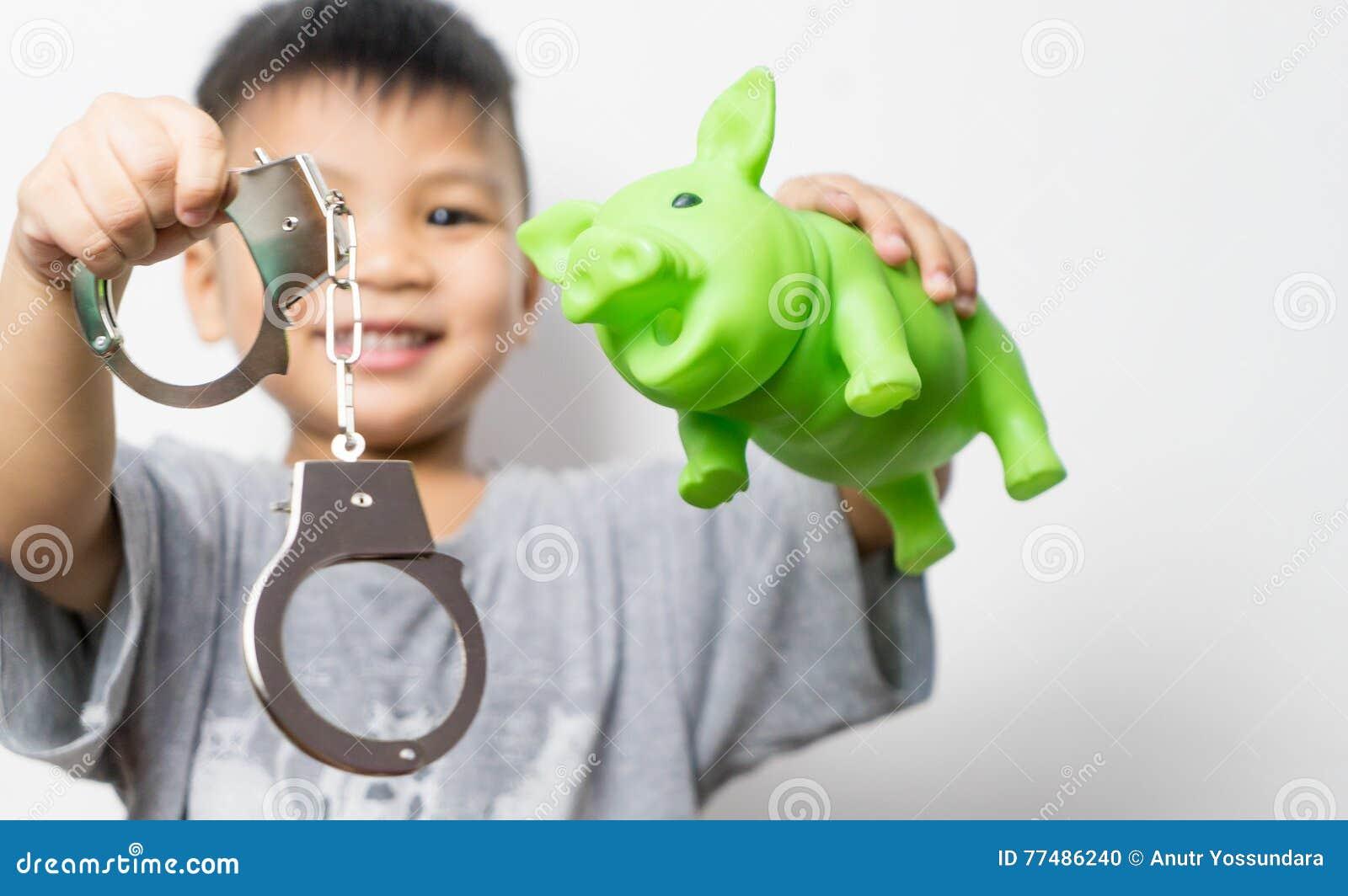 De Aziatische keus van het spaarvarken en handcuff van de jongensholding tussen goede onderwijs en misdaad