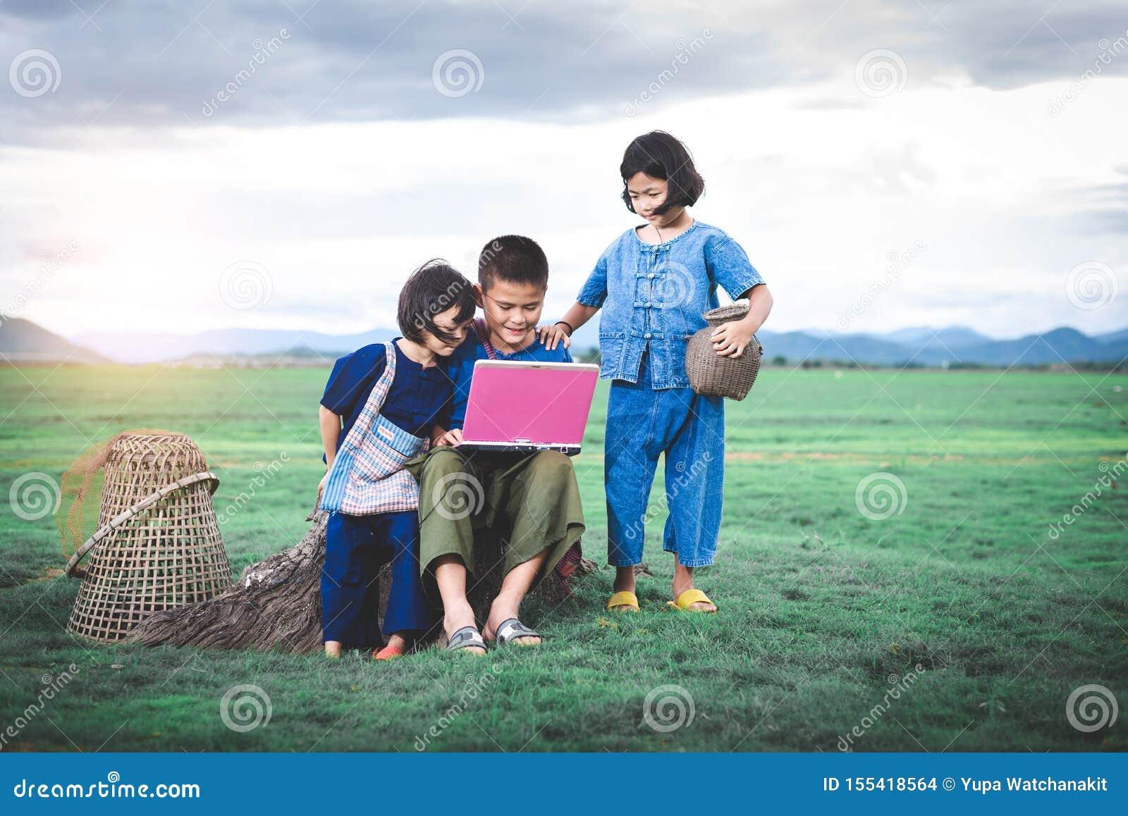 De Aziatische kinderen in lokale kleding gebruiken laptop voor onderwijs en mededeling