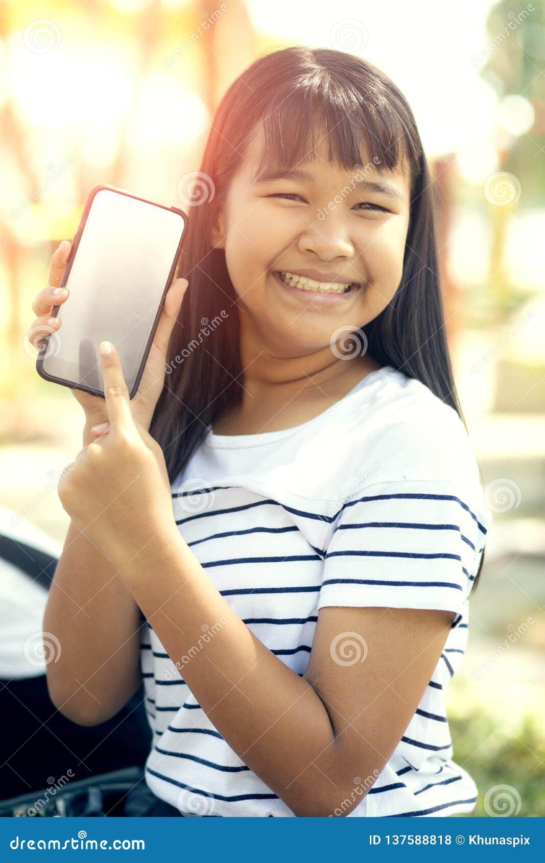 De Aziatische tiener toont het witte scherm van het smartphonescherm en toothy het glimlachen emotie van het gezichtsgeluk