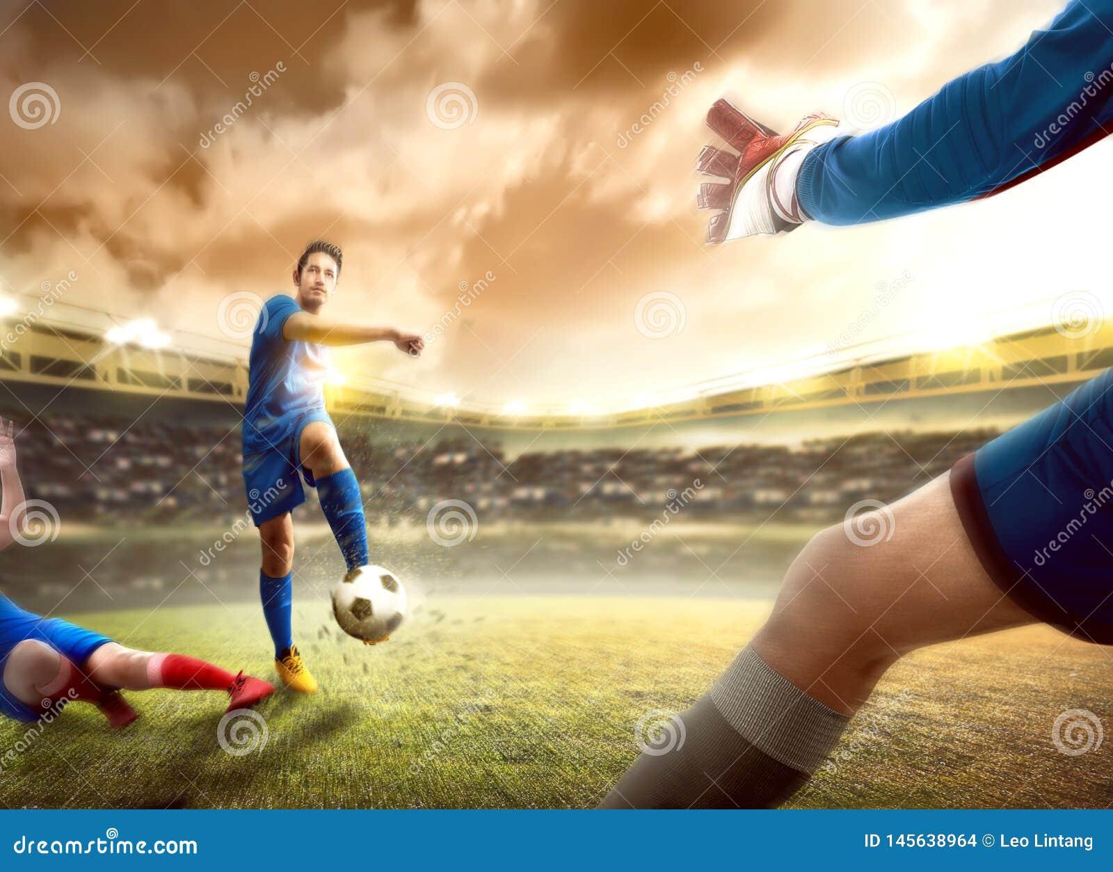 De Aziatische voetbalstermens die pakt de bal van zijn tegenstander vóór hem aan die de bal schoppen aan het doel glijden