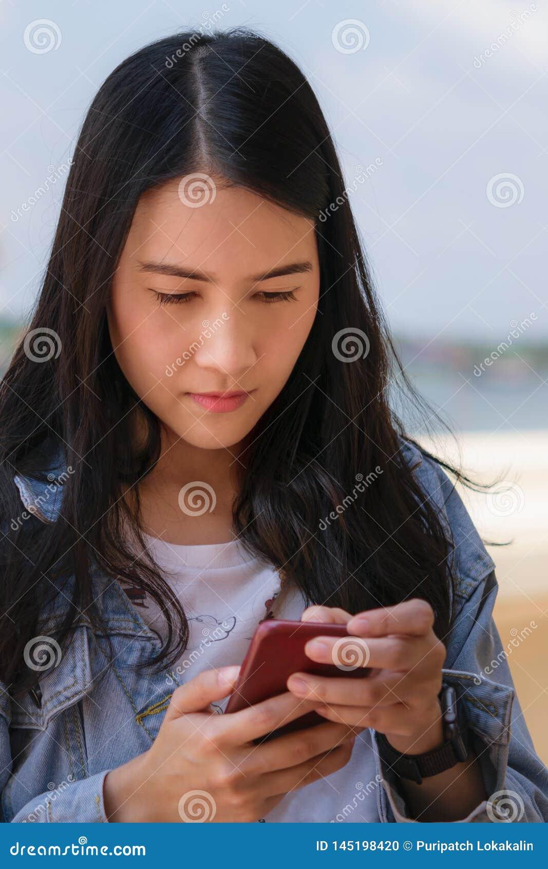 De Aziatische vrouw gebruikt smartphone
