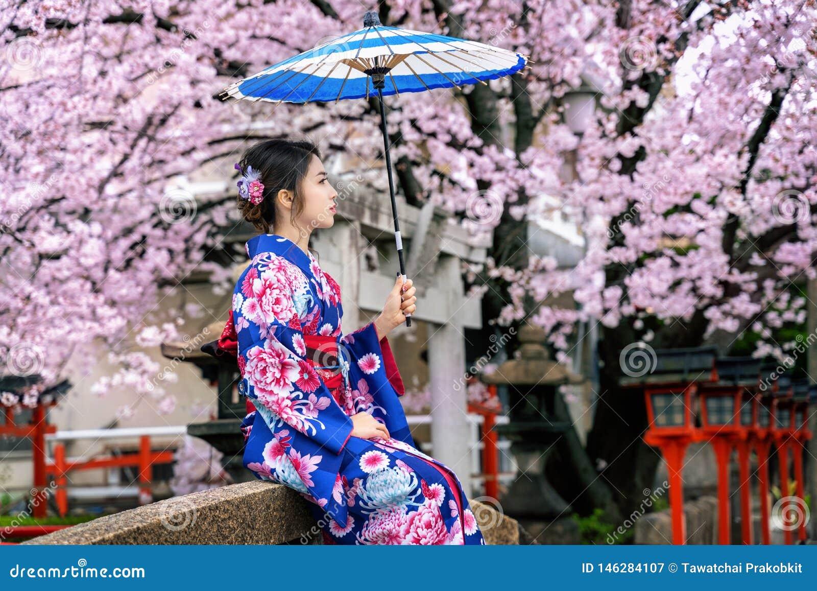 De Aziatische vrouw Japanse traditionele kimono dragen en de kers die komen in de lente, de tempel van Kyoto in Japan tot bloei