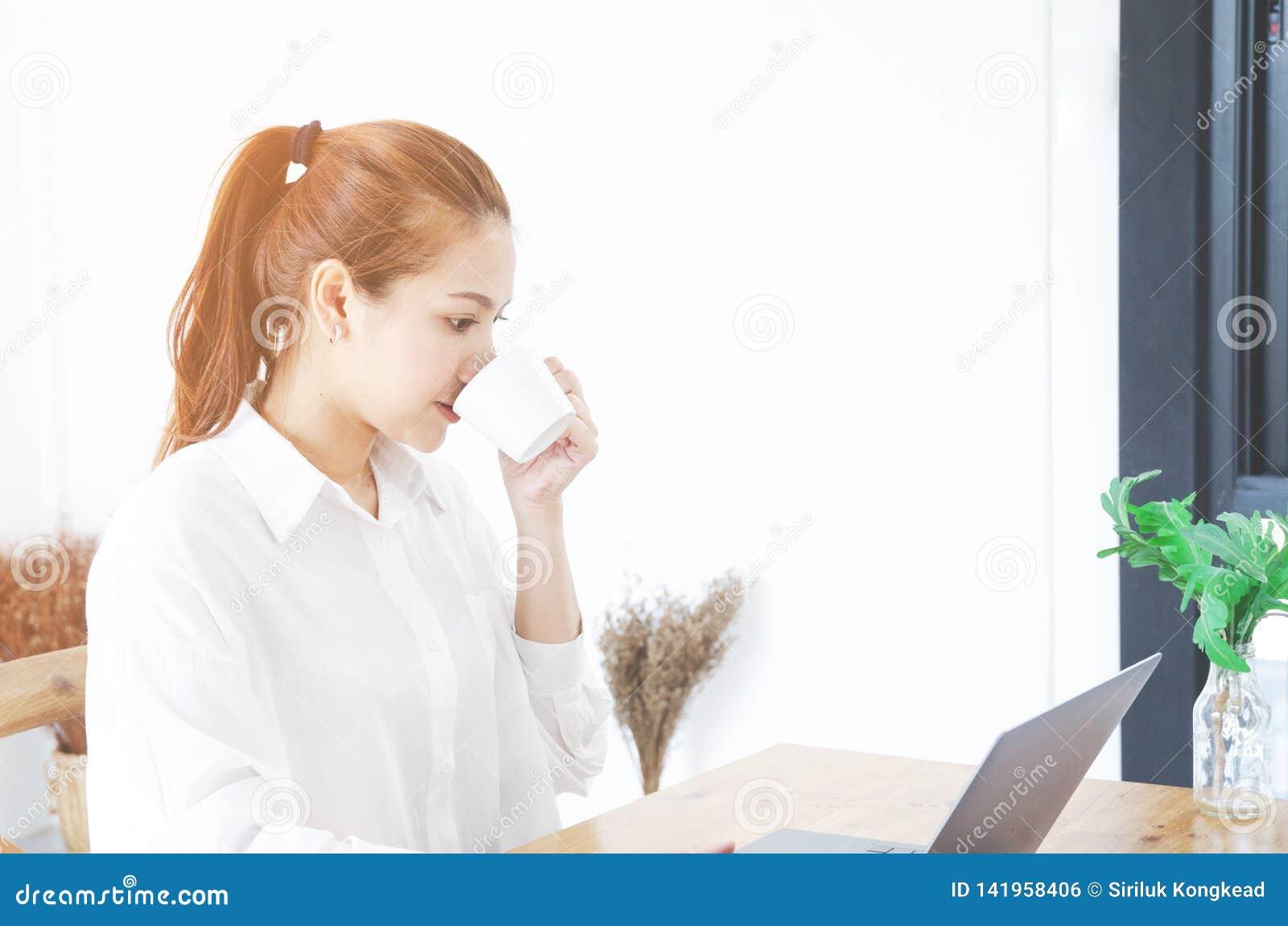 De Aziatische vrouwen die een wit overhemd dragen werkt en nipt koffie