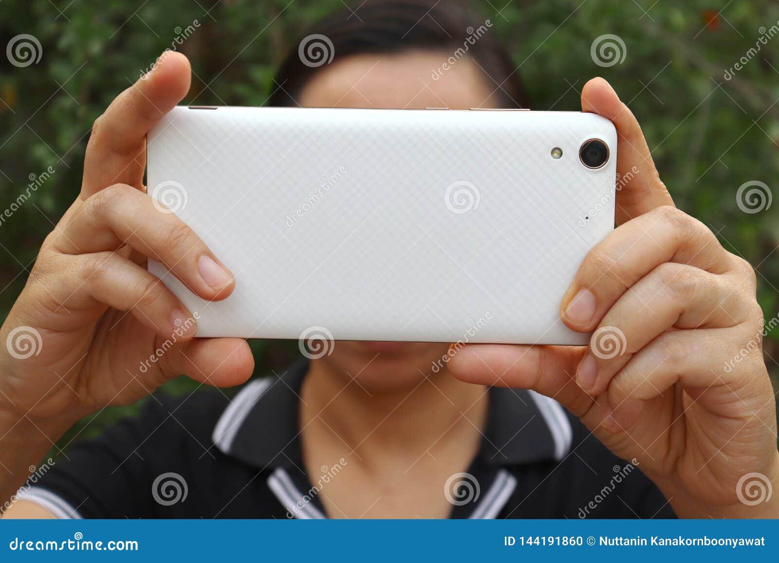 De Aziatische vrouwenholding en het gebruiken van smartphone tonen achterkant