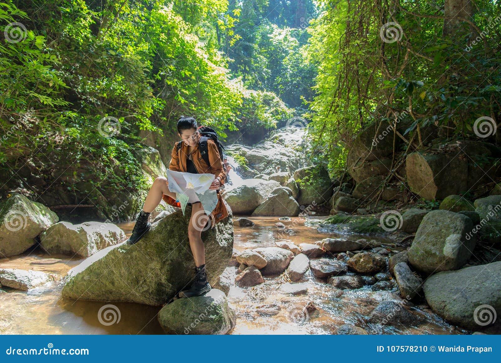 De Aziatische Vrouwenwandelaar met rugzak controleert kaart om richtingen op wildernisgebied bij watervallen te vinden