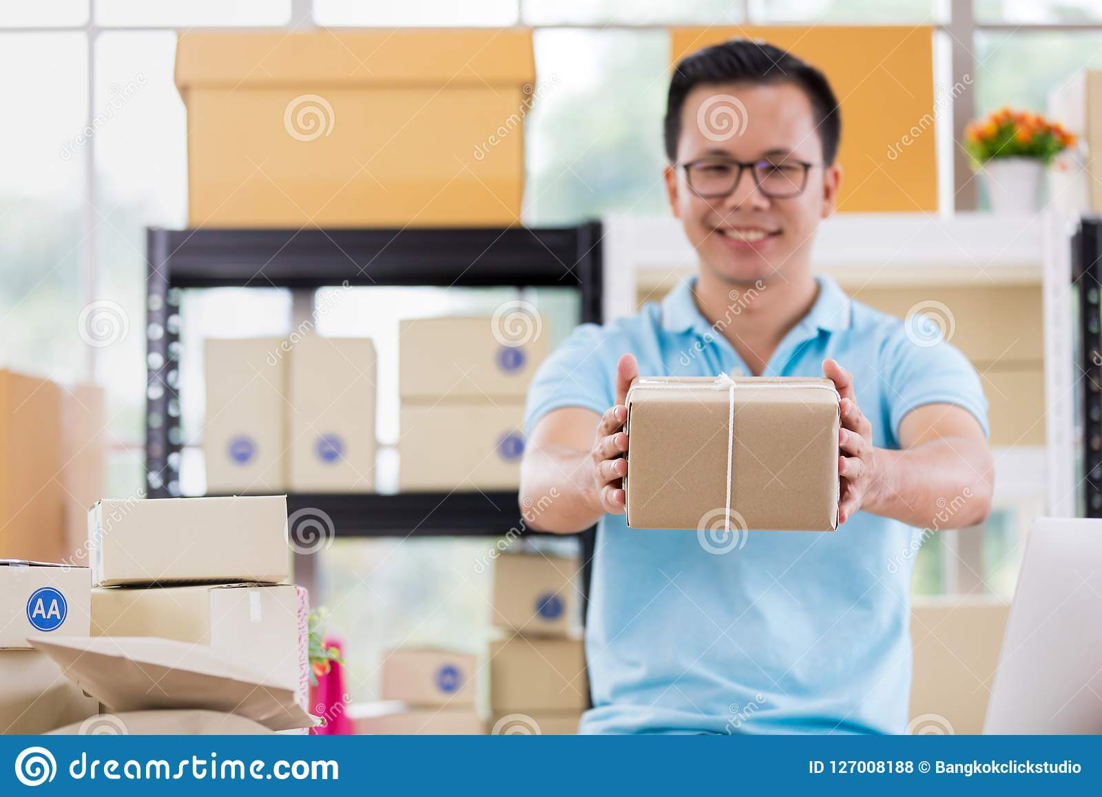 De Aziatische zakenman in toevallig overhemd was inpakt pakketten, workin