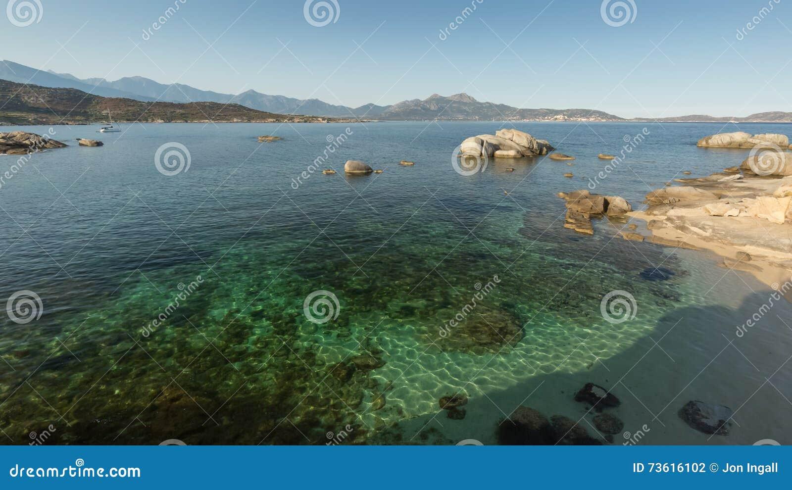 De baai van Calvi in Corsica met ondiep water en rotsen