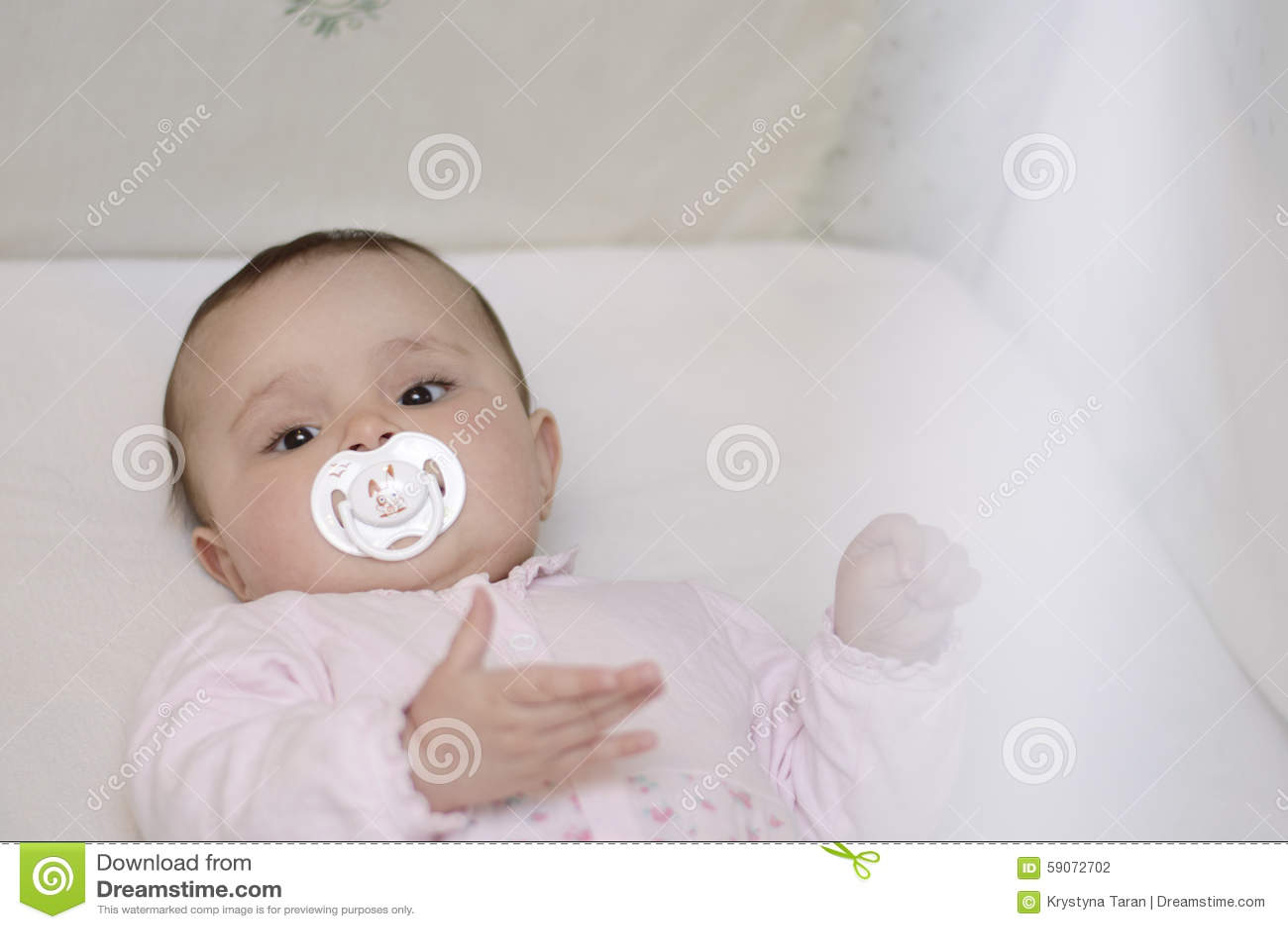 De baby ligt in de voederbak met fopspeen