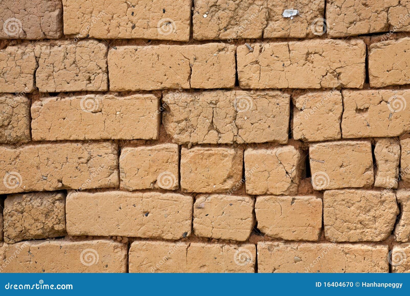 De bakstenen muur van de adobe
