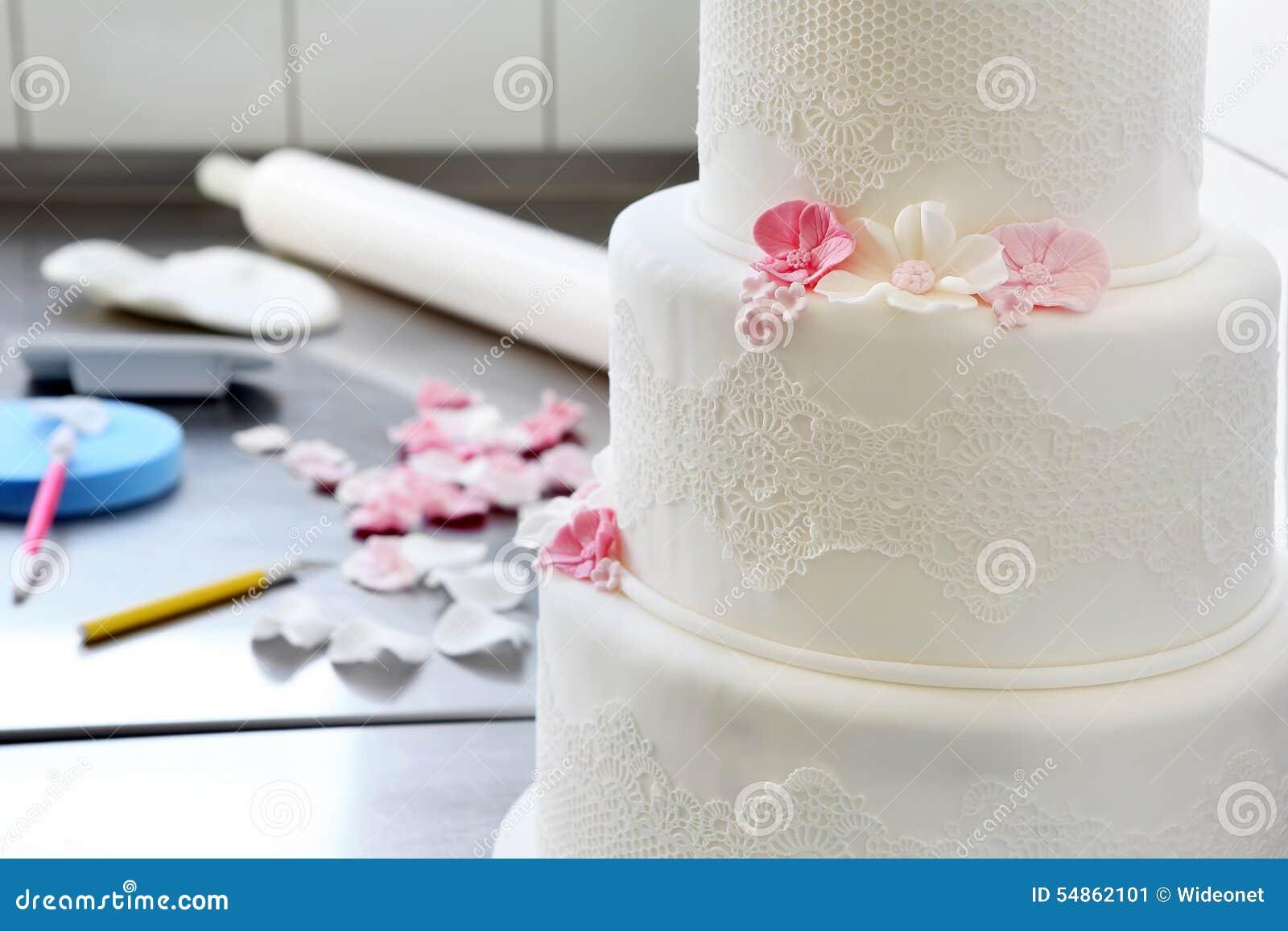 De banketbakker verfraait huwelijkscake in bakkerij