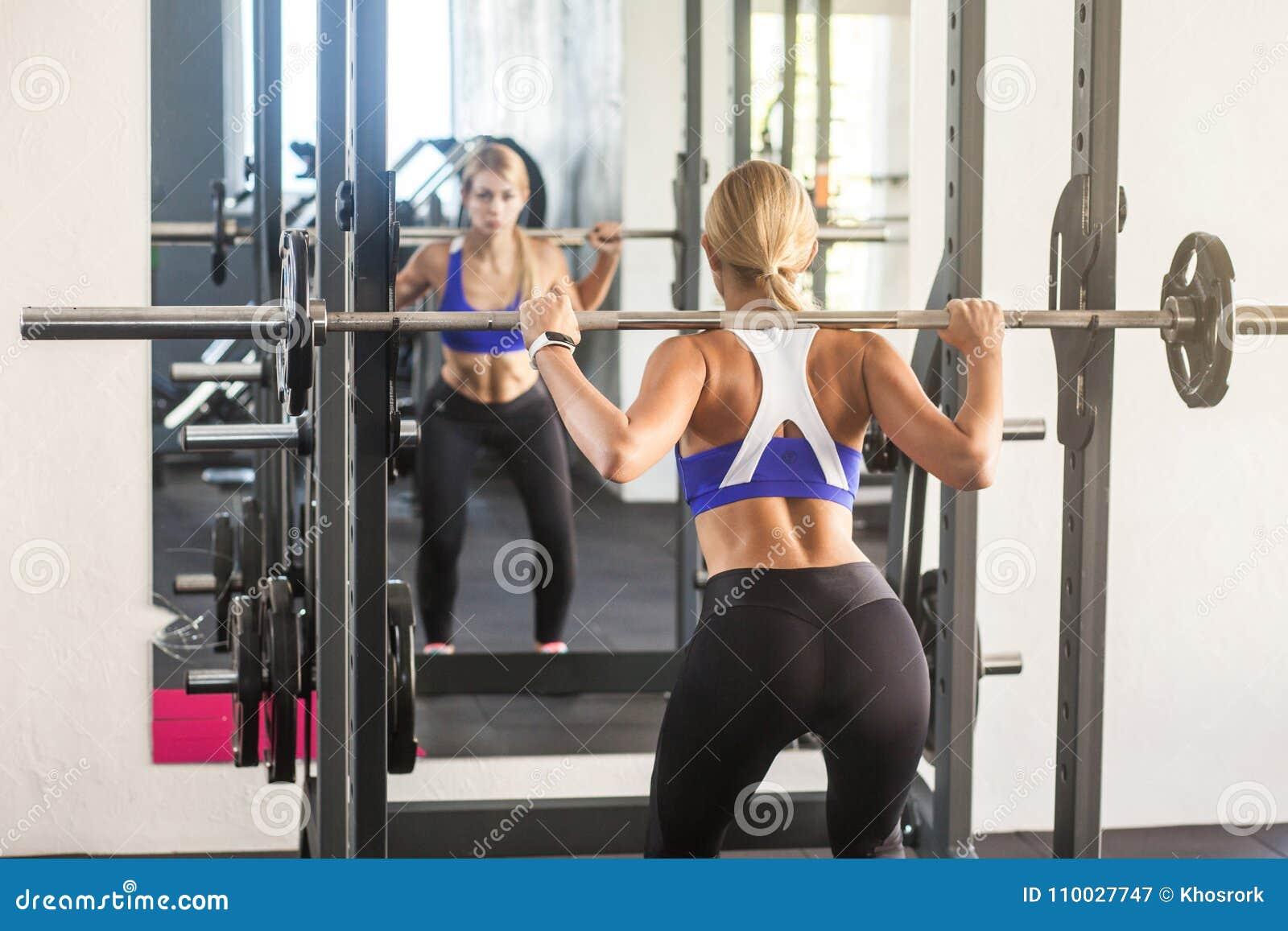 De bar van de vrouwenholding, die hurkzit doen, die spiegel kijken