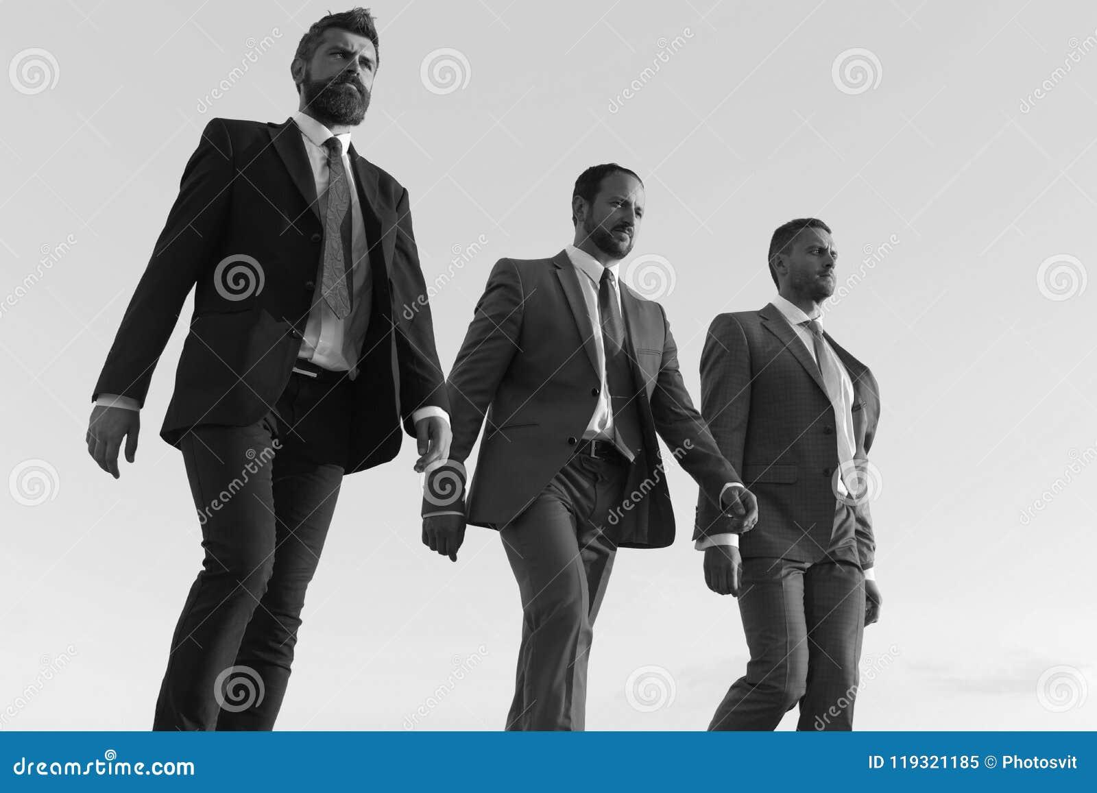 De bedrijfleiders maken stap aan succes op blauwe hemelachtergrond Bedrijfssucces en samenwerkingsconcept Zakenlieden met